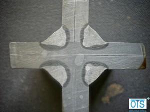 Wytrawiona próbka z ujawnionymi kształtami spoin i strefy wpływu ciepła.